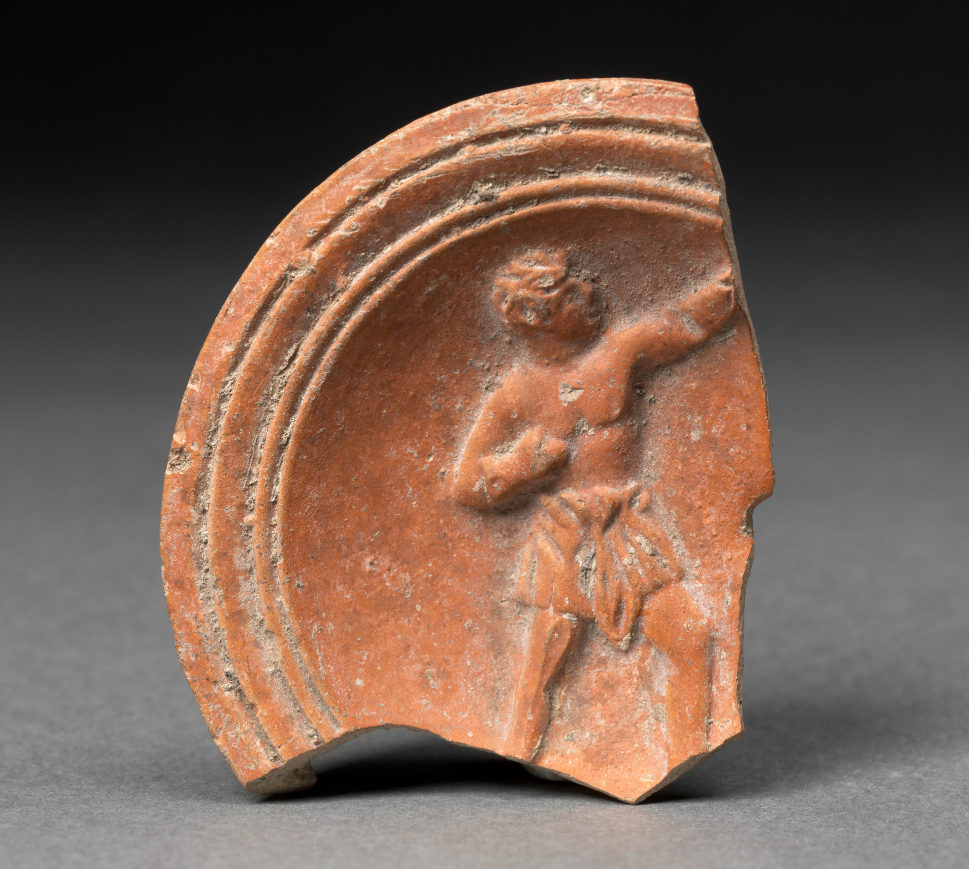 Unknown (Roman), Fragment from an oil lamp with boxer motif, 40-100 CE. Terracotta, 2 1/4 x 1 15/16 x 3/8 in. Gift of Charles Caryl Coleman. (28.8.7)