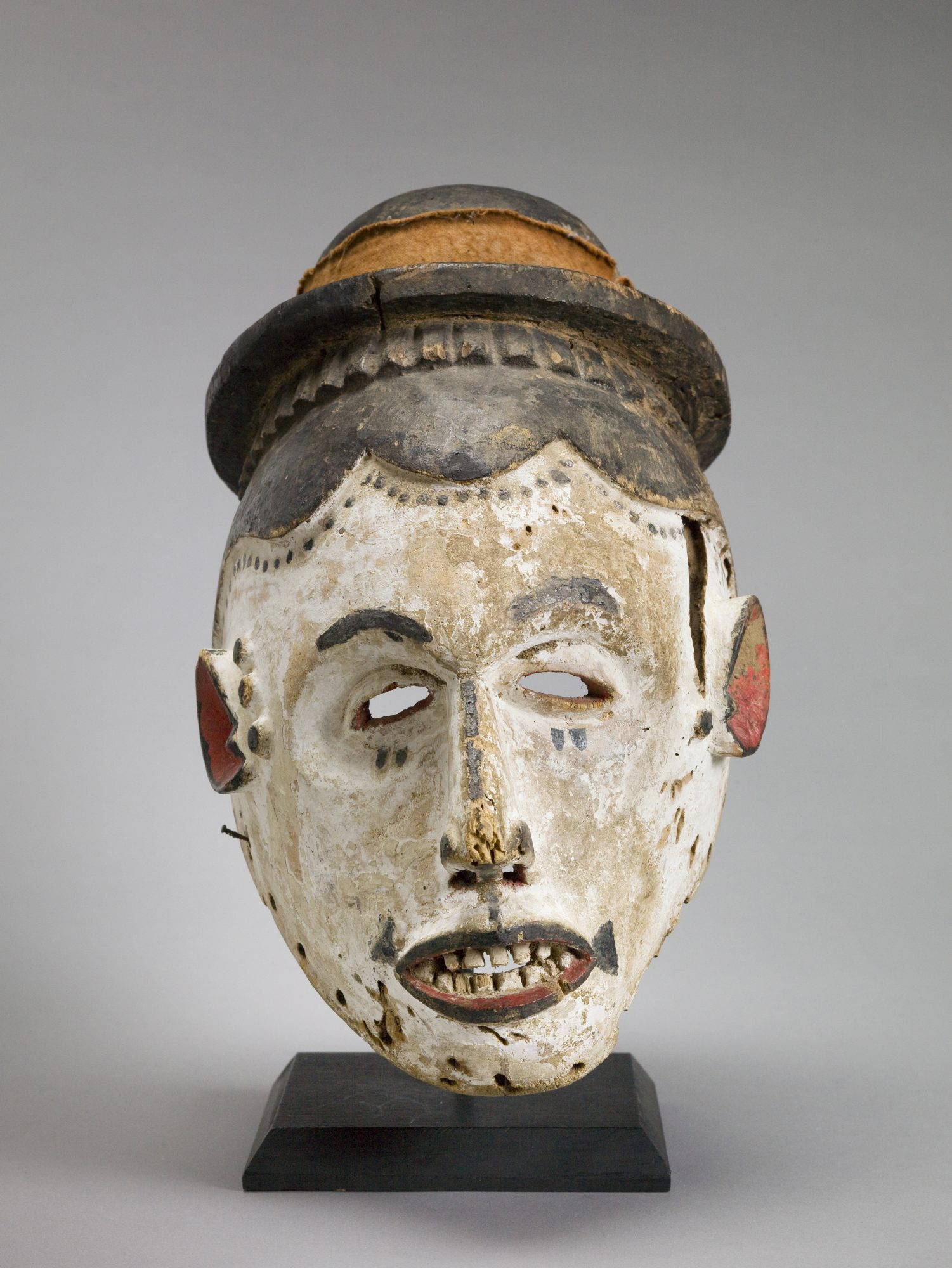 Igbo People, Helmet Mask, 20th Century, wood, pigment, and cloth. Gift of Robert and Suzanne Bach.