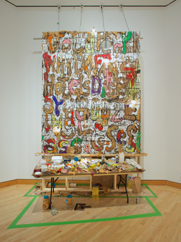 William Pope.L (American, b. 1955) Mudder of Excess Part B, 2017 Peanut butter, vegetable oil, oil paint, acrylic, charcoal, graphite, joint compound, and tape on masonite with light bulbs, electrical cords, wood, and hardware Courtesy of the artist and Mitchell-Innes & Nash and Susanne Vielmetter Los Angeles Projects