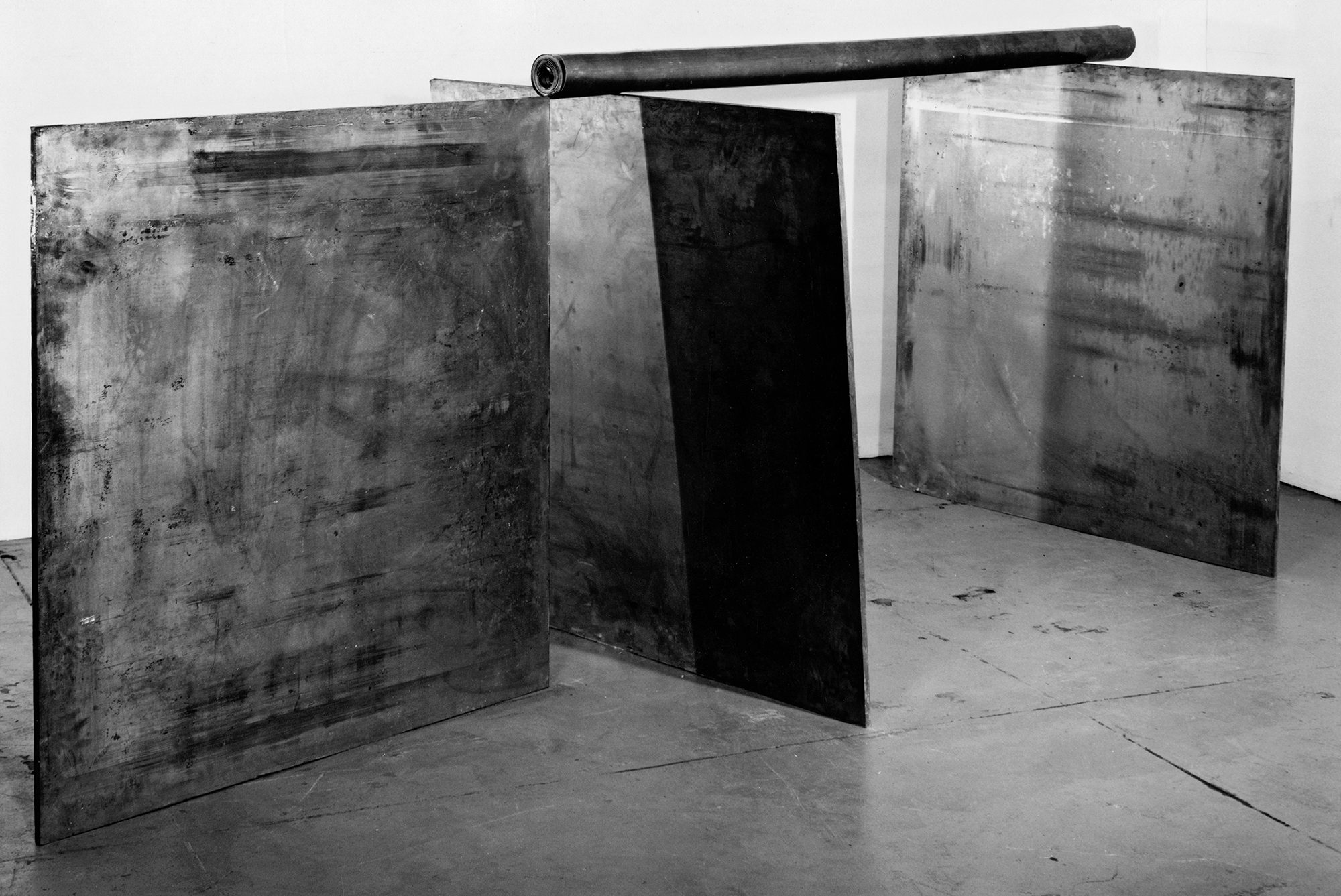 Richard Serra (American, b. 1939), 1-1-1, 1969. Lead, three plates: each: 48 x 48 x 1 in., pole: 84 in. long, 4 in. diameter. Photo by Peter Moore. Collection of the artist.